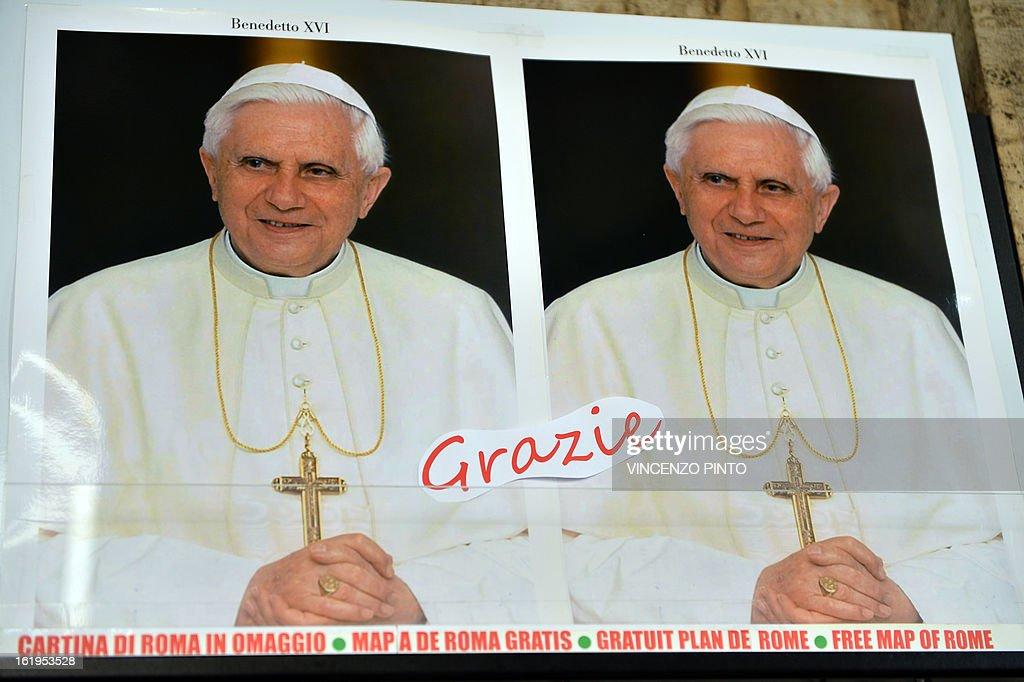 A note reading 'Thank you' had been sticked on portraits of Pope Benedict XV I on pôrtraits outside a souvenirs shop near the Vatican on Febraury 18, 2013 in Rome. Pope Benedict XVI began a week-long spiritual retreat out of the public eye on Monday ahead of his resignation on February 28, with the field of candidates to succeed him still wide open. AFP PHOTO / VINCENZO PINTO