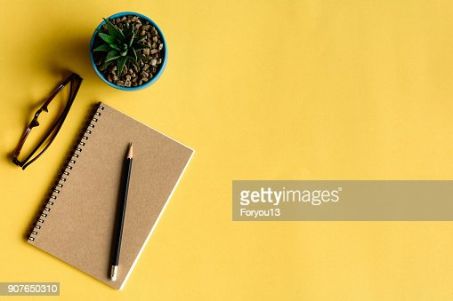 notebook and pencil on yellow desk : Stock Photo