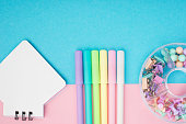 Notebook, pen, paper clips on pastel paper background. Top view. Place for text. Horizontal