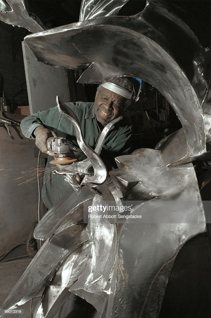 Noted African American sculptor Richard Hunt grinds and polishes a metal sculpture while at a foundry or studio, Chicago, IL, 2000.