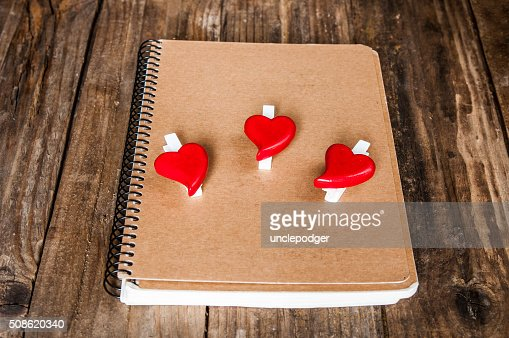 Notepad and hearts on grunge wooden background : Stock Photo