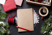 Notepad for christmas letter, gift box wrapping, snow fir tree and coffee cup. Top view with copy space