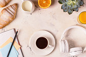 Notepad, headphones, croissants and coffee on white table. Top view with copy space.