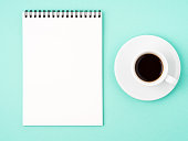 Notepad open with white blank page for writing idea or to-do list, a Cup of coffee  on bright blue background