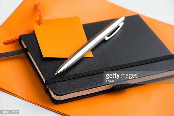 Notizblock und Stift auf eine orange-Tasche