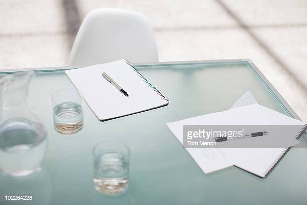 Notepads and pens on conference table