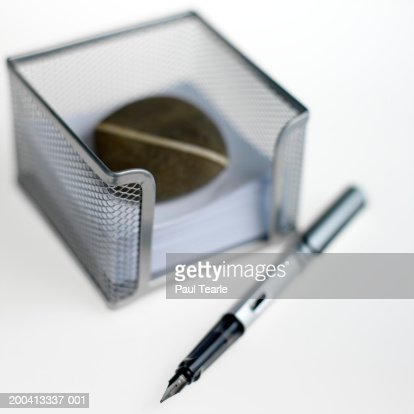 Notepaper in holder with paperweight and fountain pen, close up