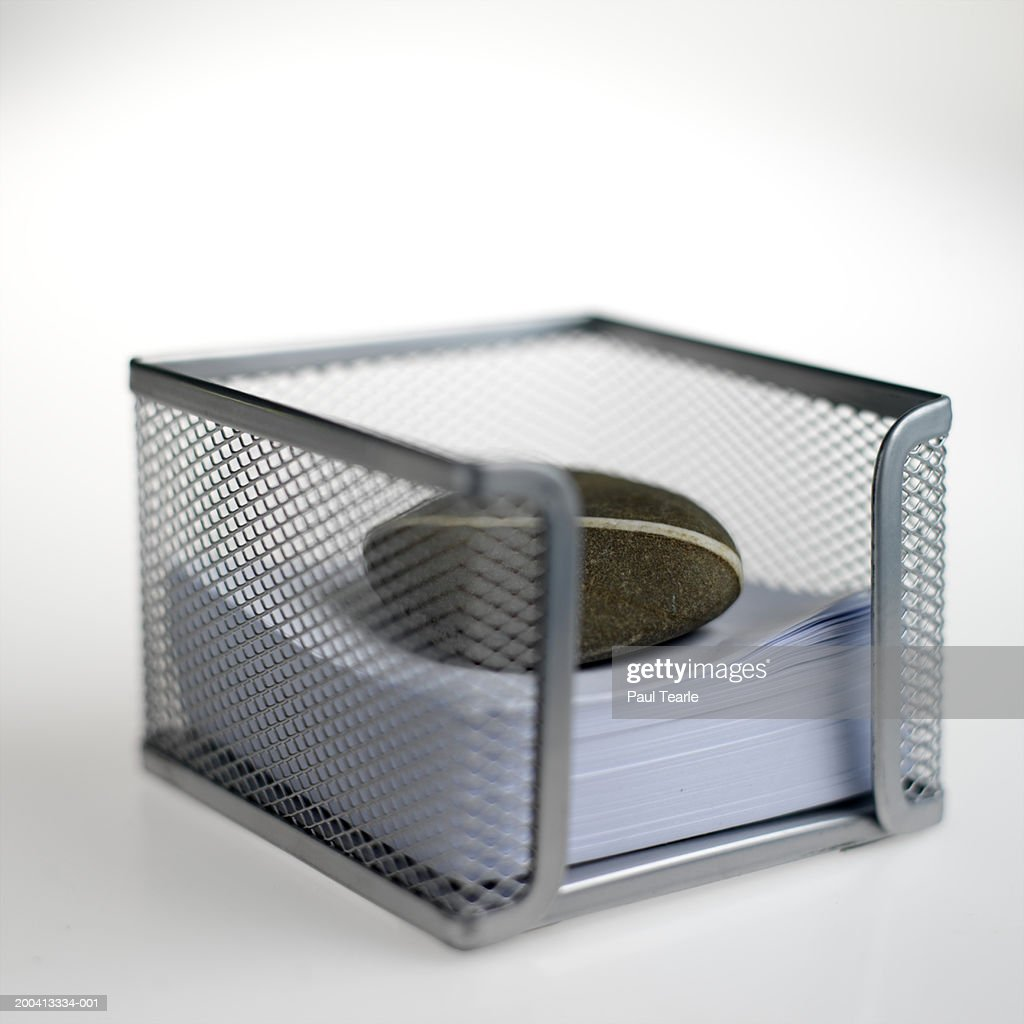 Notepaper in holder with paperweight, close up
