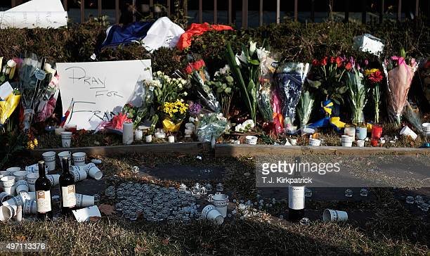 Notes of support bouquets and bottles of wine fill a makeshift memorial at the entrance of the French Embassy on November 14 2015 in Washington DC A...