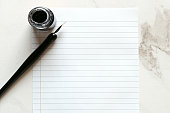 Blank lined paper with ink well and fountain pen