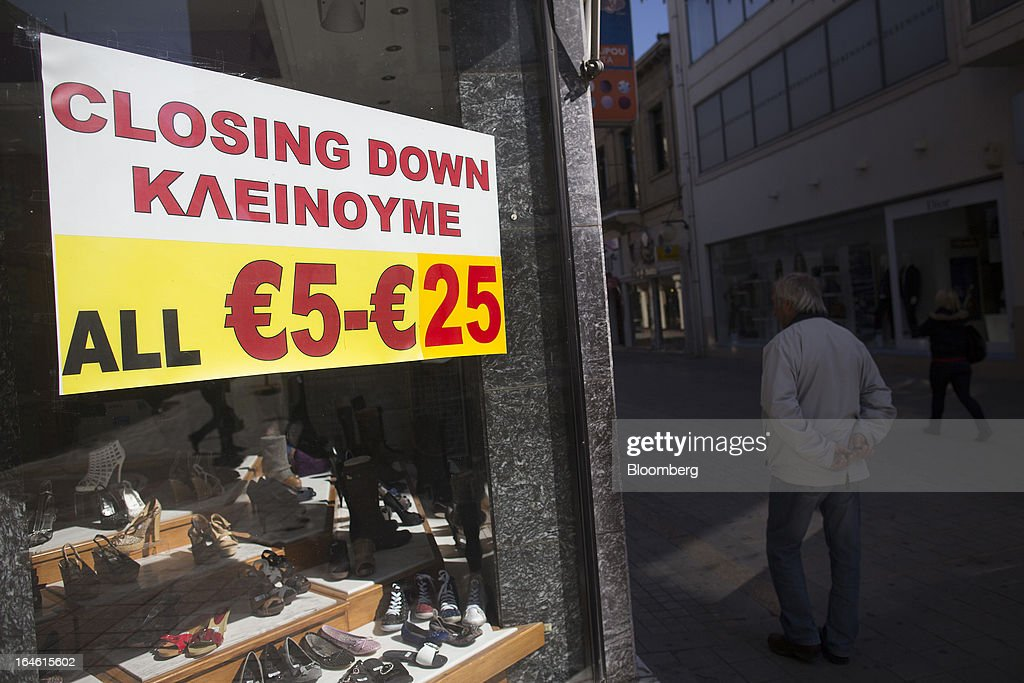 A notice advertising euro discounts sits in the window of a retail store which is closing down in Nicosia, Cyprus, on Monday, March 25, 2013. In a replay of tensions over aid for Greece at the outset of the crisis, European governments had wrangled over aid for Cyprus for nine months, exposing holes in the revamped economic management system that was built in three years of emergency policymaking, often at all-night summits. Photographer: Photographer: Simon Dawson/Bloomberg via Getty Images
