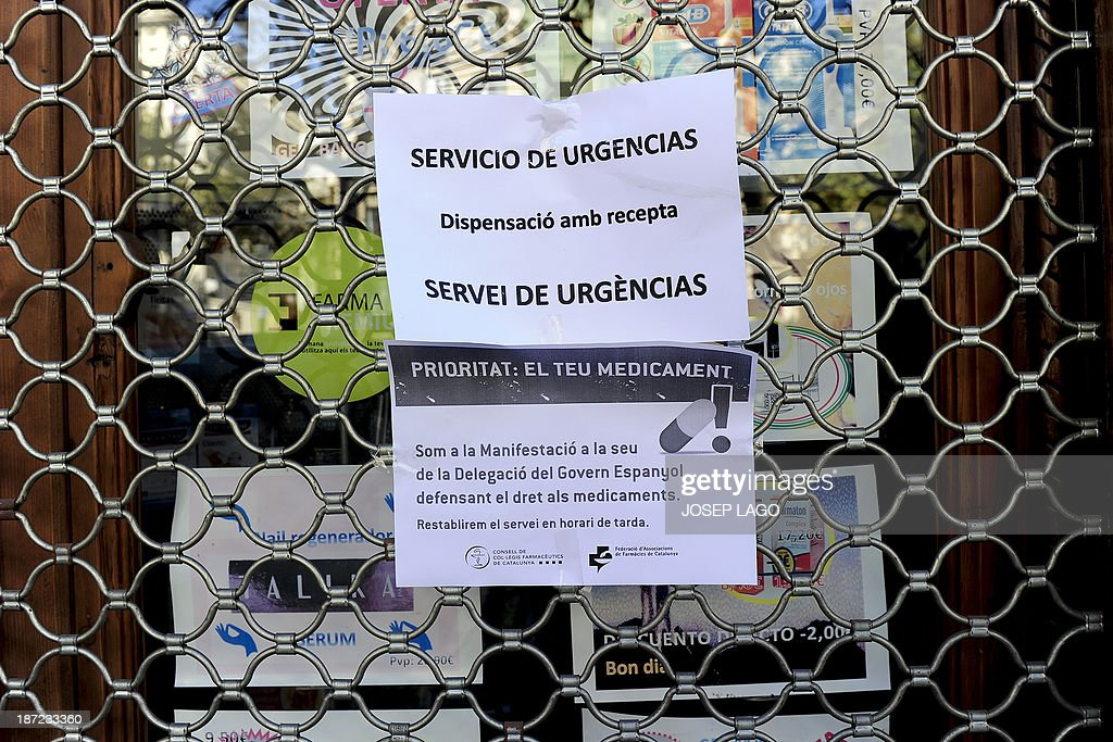A notice on the gate of a closed pharmacy in Barcelona reads 'Emergency Service' on November 7, 2013 rmacy during a strike against the non-payment of the Spanish government.