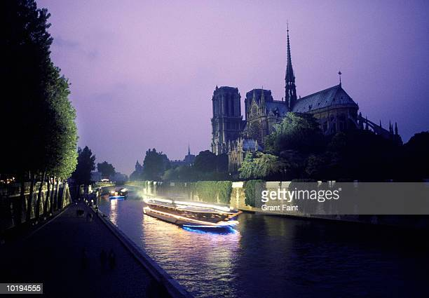 Notre Dame and tour boat on the river Siene at night, Paris, France