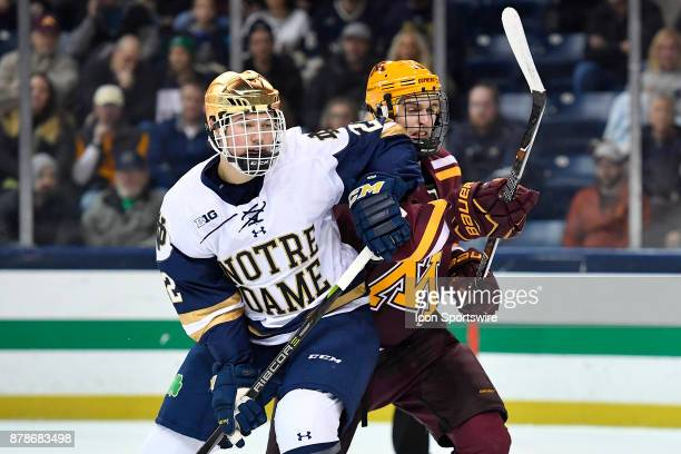 Notre Dame Fighting Irish defenseman Andrew Peeke and Minnesota Golden Gophers forward Scott Reedy fight for position during the game between the...