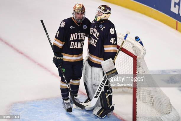 Notre Dame Fighting Irish defenseman Dennis Gilbert talks with Notre Dame Fighting Irish goalie Cal Petersen after a Denver Pioneers' goal in the...