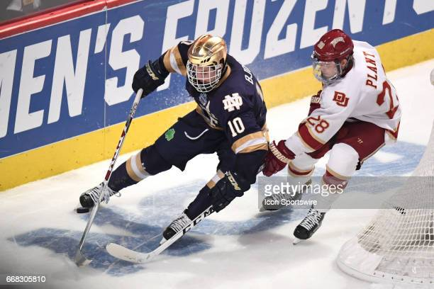 Notre Dame Fighting Irish forward Anders Bjork controls the puck next to Denver Pioneers defenseman Adam Plant in the second period of an NCAA Frozen...