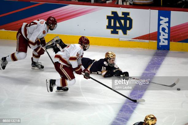 Notre Dame Fighting Irish forward Anders Bjork falls to the ice as he reaches out to get tot he puck with this stick with Denver Pioneers forward...