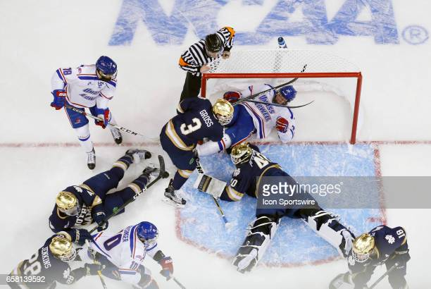 Notre Dame Fighting Irish goaltender Cal Petersen covers the puck with UMass Lowell River Hawks left wing Jake Kamrass in the goal during the NCAA...