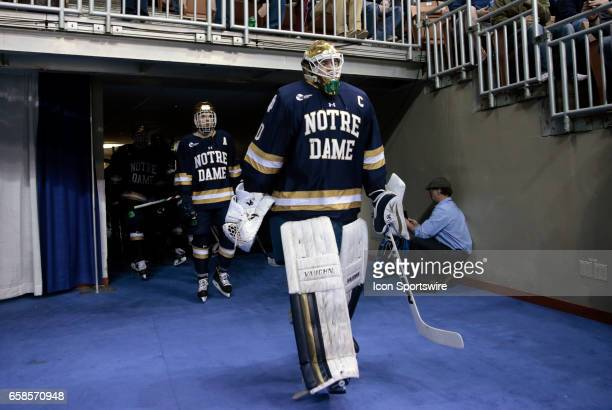 Notre Dame Fighting Irish goaltender Cal Petersen leads his team onto the ice during the NCAA Northeast Regional final between the UMass Lowell River...