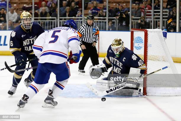 Notre Dame Fighting Irish goaltender Cal Petersen makes a save with UMass Lowell River Hawks center Joe Gambardella on the doorstep during the NCAA...