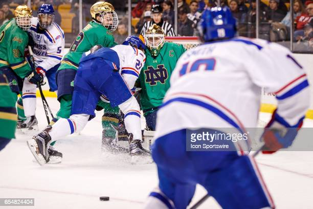 Notre Dame Fighting Irish goaltender Cal Petersen watches a loose puck while fighting for position with UMass Lowell Riverhawks forward Jake Kamrass...