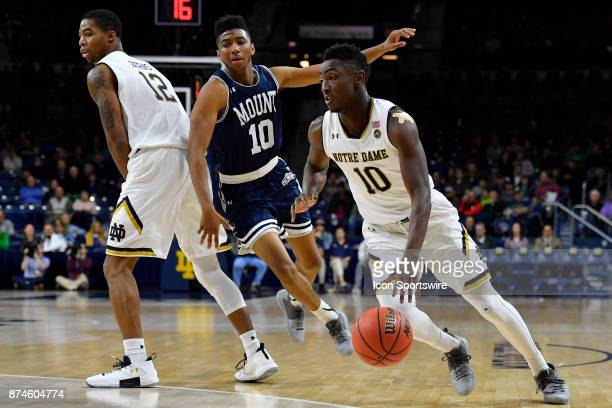 Notre Dame Fighting Irish guard Temple Gibbs dribbles the ball around the pick set by Notre Dame Fighting Irish's Elijah Burns during the game...