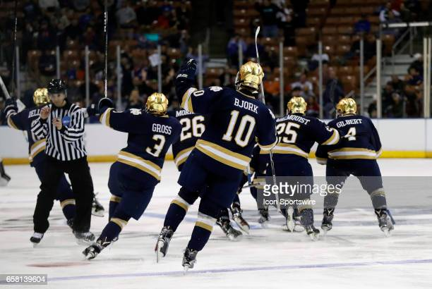 Notre Dame Fighting Irish right wing Anders Bjork and teammate celebrate the overtime winner from Notre Dame Fighting Irish center Andrew Oglevie...