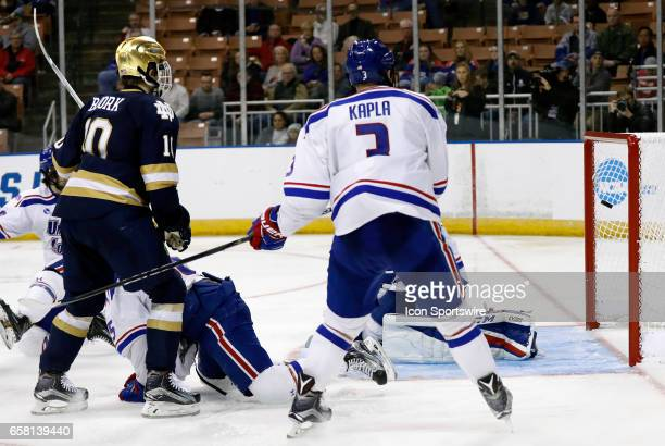 Notre Dame Fighting Irish right wing Anders Bjork and UMass Lowell River Hawks defenseman Michael Kapla watch the shot from Notre Dame Fighting Irish...