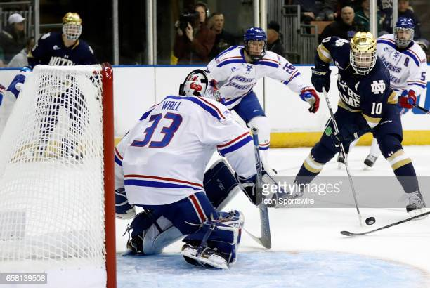 Notre Dame Fighting Irish right wing Anders Bjork puts a shot on UMass Lowell River Hawks goaltender Tyler Wall during the NCAA Northeast Regional...