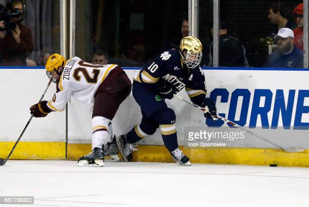 Notre Dame Fighting Irish right wing Anders Bjork turns away from Minnesota Golden Gophers defenseman Ryan Zuhlsdorf during an NCAA Northeast...