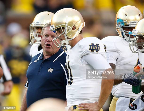 Notre Dame head coach Brian Kelly talks with quarterback Tommy Rees of the Fighting Irish before playing the Michigan Wolverines at Michigan Stadium...