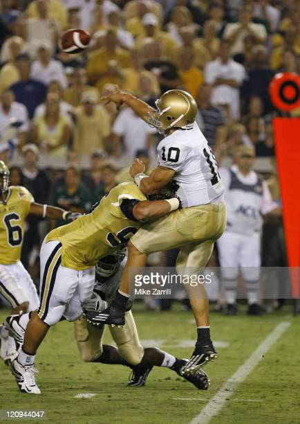 Notre Dame QB Brady Quinn lets go of a pass after being hit by a Georgia Tech defender during the game at Grant Field at Bobby Dodd Stadium in...