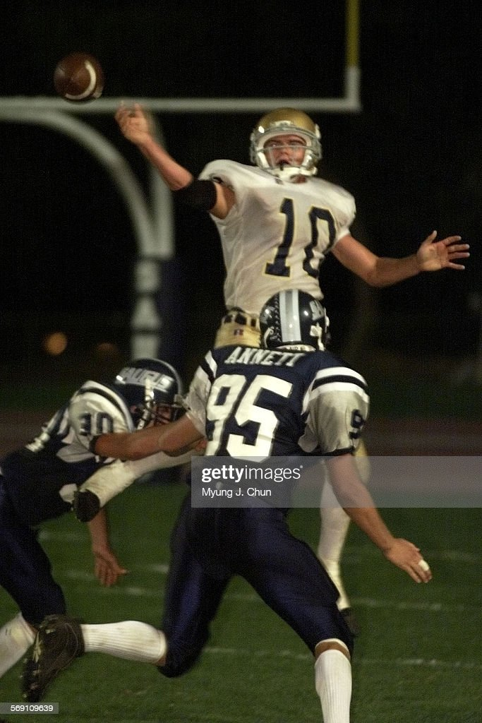 Notre Dame QB Phil Beckmann throws the ball away in the third quarter following pressure from Saugus defenders Sean Himes and Adam Annett DIGITAL...