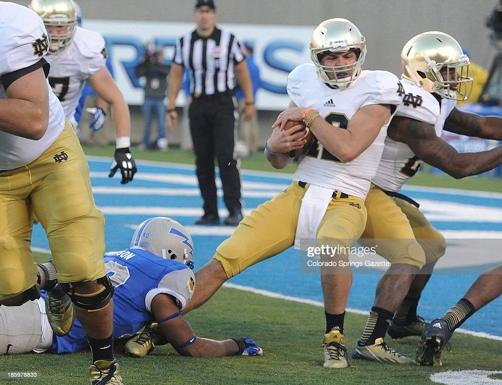 Notre Dame quarterback Andrew Hendrix backs in for a touchdown in the fourth quarter as Air Force defensive lineman Ryan Watson, left, tries to bring him down at Falcon Stadium in Colorado Springs, Colorado, on Saturday, October 26, 2013. Notre Dame won, 45-10.