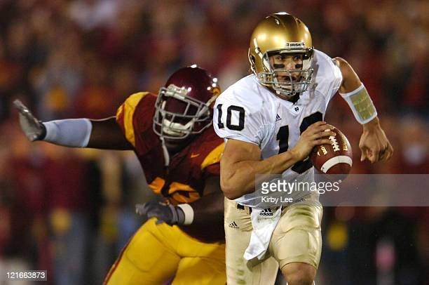 Notre Dame quarterback Brady Quinn scrambles from Sedrick Ellis during 4424 loss at the Los Angeles Memorial Coliseum in Los Angeles Calif on...