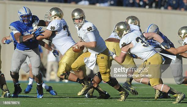 Notre Dame quarterback Tommy Rees gets ready to hand off to running back Cam McDaniel as Air Force defensive lineman Robert Green closes in during...