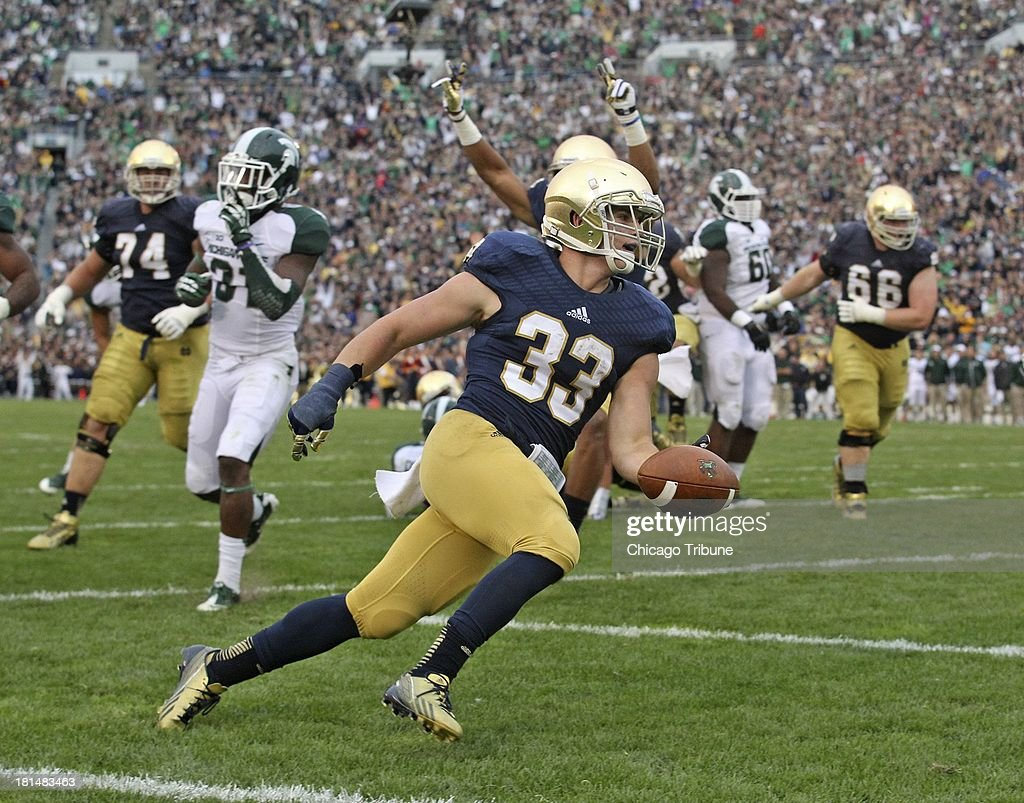 Notre Dame running back <a gi-track='captionPersonalityLinkClicked' href=/galleries/search?phrase=Cam+McDaniel&family=editorial&specificpeople=9937391 ng-click='$event.stopPropagation()'>Cam McDaniel</a> (33) celebrates his 7-yard touchdown run in the second half against Michigan State at Notre Dame Stadium in South Bend, Indiana, on Saturday, September 21, 2013. The Fighting Irish won, 17-14.