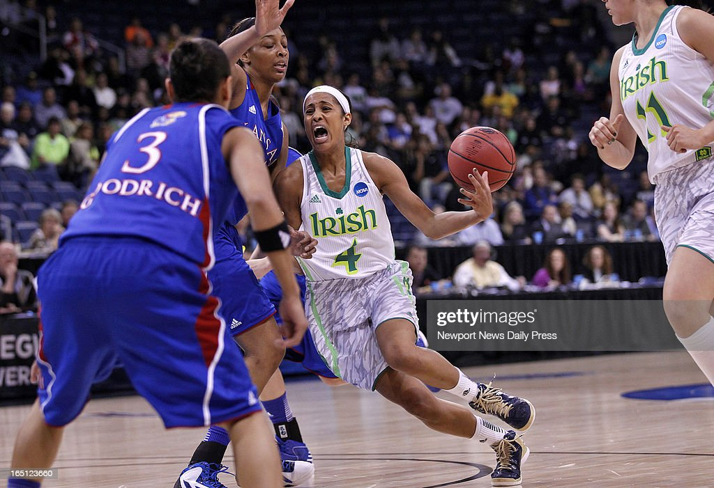 Notre Dame's Skylar Diggins, center, loses control of the ball while running into the defense of Kansas' Angel Goodrich, left, and Carolyn Davis, center, during Sunday's NCAA women's basketball regional semifinal on March 31, 2013, at the Ted Constant Center in Norfolk, Virginia.