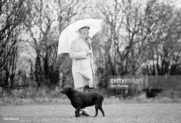 Nottingham Forest assistant manager Peter Taylor with his labrador Bess watching a training session in rainy Nottingham circa November 1980