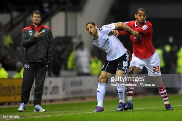 Nottingham Forest manager Steve Cotterill points towards his player Dexter Blackstock and Derby Countys Nathan Tyson as they tussle with each other...