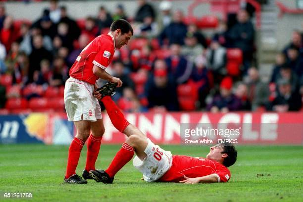 Nottingham Forest's Francis Benali helps teammate Keith Foy overcome his cramp