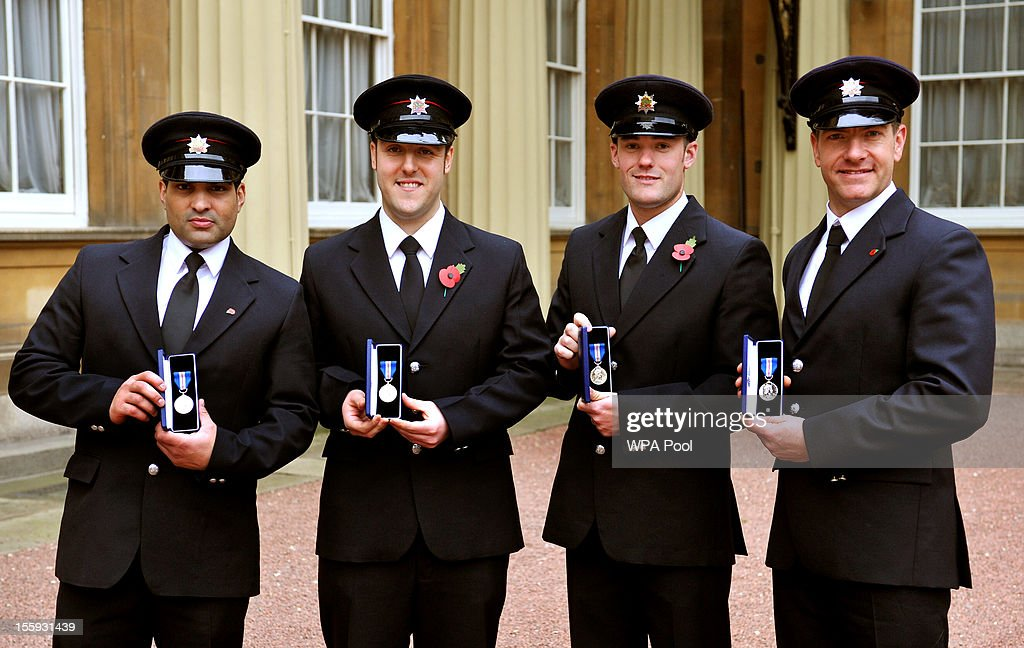 Nottinghamshire Firemen Sanjeev Mohia, Daniel Wareham, Matthew Willis and Andrew Alexander with their Queen's Gallantry Medals, presented to them by Queen Elizabeth II at an investiture ceremony at Buckingham Palace on November 9, 2012 in London, England.