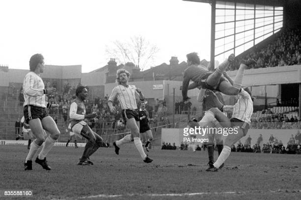 Notts County goalkeeper Mick Leonard flies out of his goal to punch the ball clear of Arsenals Tony Woodcock and teammate David Clarke Also pictured...