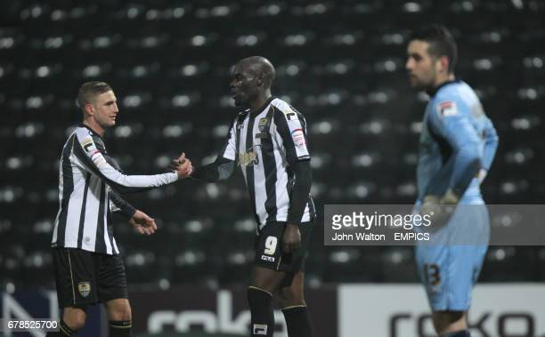 Notts County's Enoch Showunmi is congratulated on scoring by teammate Gary Liddle as Oldham Athletic's goalkeeper Dean Bouzanis stands dejected