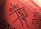 Noughts and crosses (tic tac toe) doodles on back of envelope
