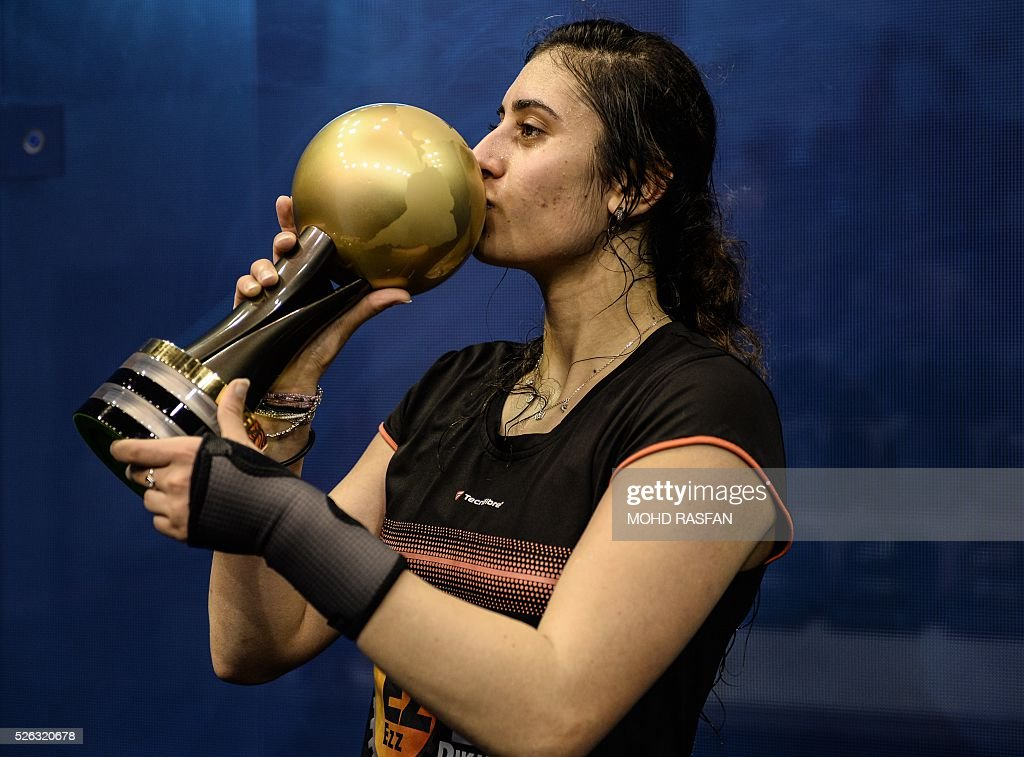 Nour El Sherbini of Egypt kisses her trophy after winning against Laura Massaro of England after their final match of the PSA Women's World Championships squash tournament in Bukit Jalil, oustide Kuala Lumpur on April 30, 2016. / AFP / MOHD