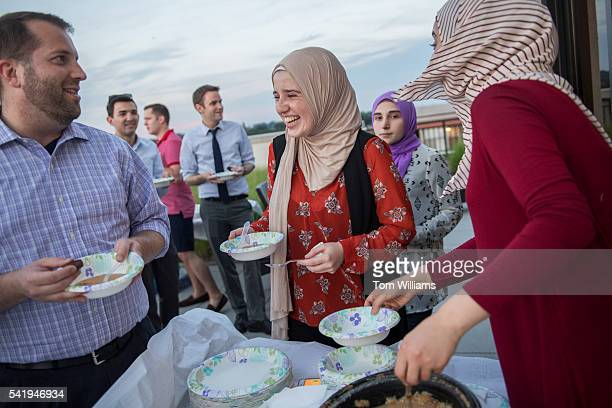 Nour Soubani center and Ghada Alkiek right dish out lentil soup during an iftar dinner on a roof deck in Northeast for guests who participated in...