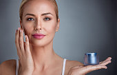 Beautiful nourished woman holding cream for her skin