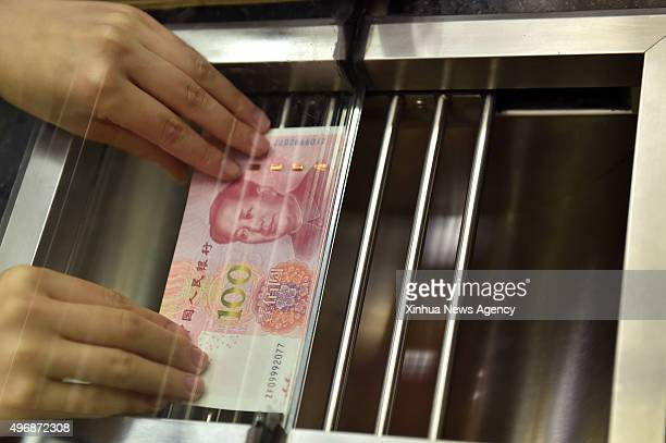 BEIJING Nov 12 2015 A bank staff member presents a new 100yuan banknote to a resident at the Beijing Branch of the Bank of Communication in Beijing...