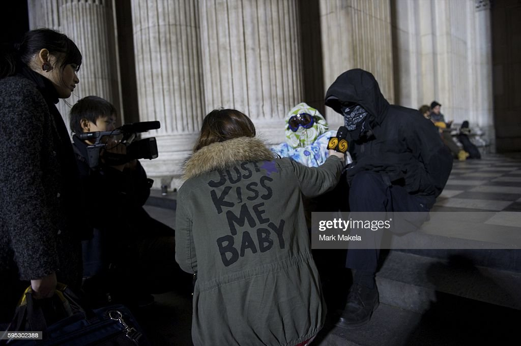 Nov 17 2011 London England UK Masked occupiers are interviewed outside St Paul's Cathedral as part of 'Occupy London' one of more than a thousand...